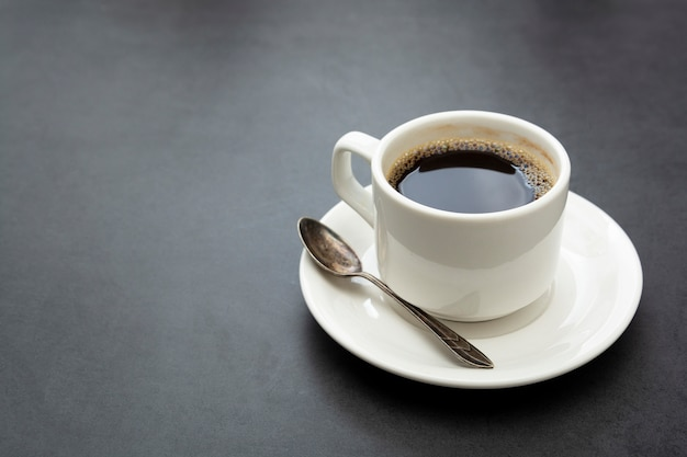 Tasse à café isolée. tasse de café blanc vue de dessus cuillère et assiette sur fond sombre