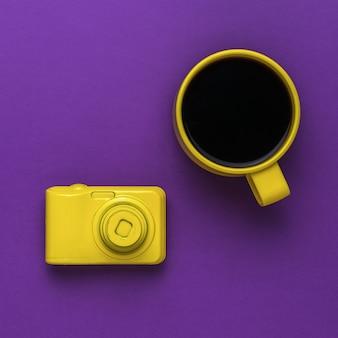 Une tasse à café jaune et un appareil photo jaune sur fond violet. mise à plat.