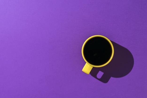 Une tasse de café jaune sur fond violet clair.