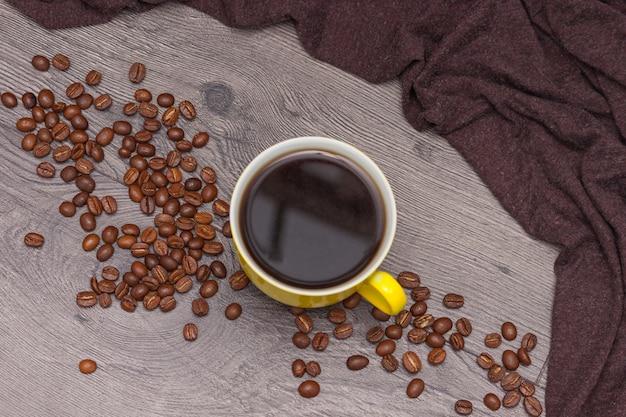 Tasse à café jaune et grains de café sur bois