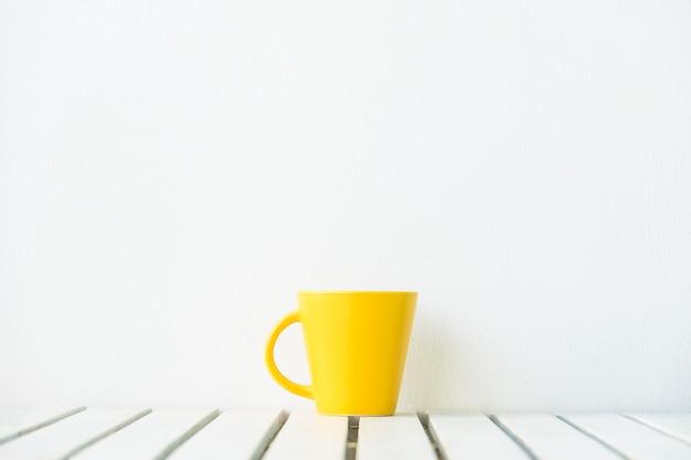 Tasse à café jaune sur la table