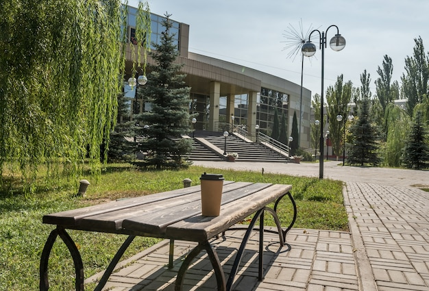 Tasse à café jetable en papier brun. se dresse sur un banc en été dans la nature.