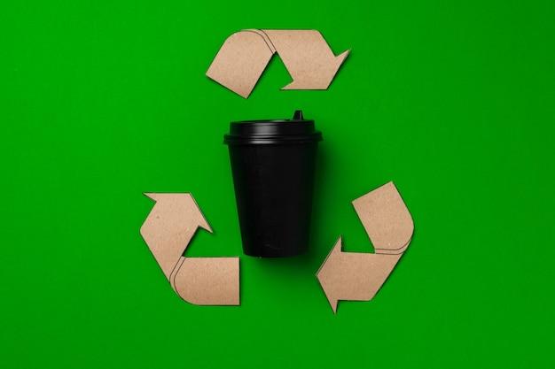 Tasse à café jetable et signe de recyclage sur fond vert