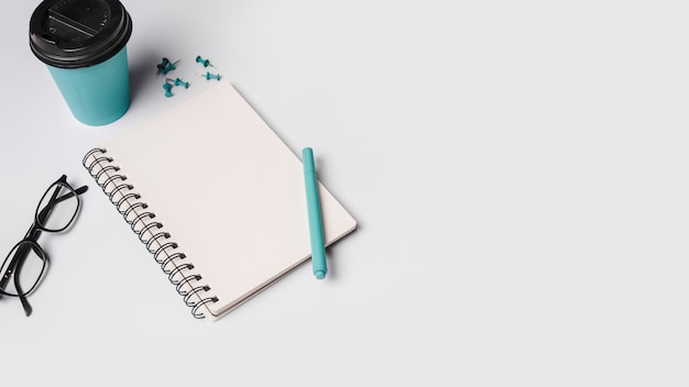 Tasse à café jetable; stylo; lunettes; bloc-notes spirale et punaises sur fond blanc