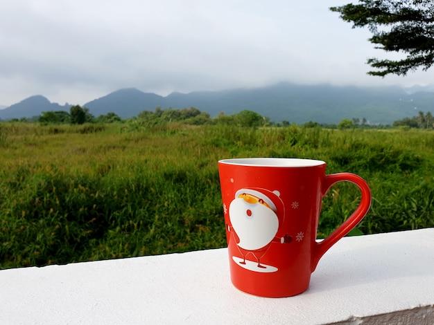 Tasse de café de joyeux noël au champ d'herbe et au point de vue de montagne
