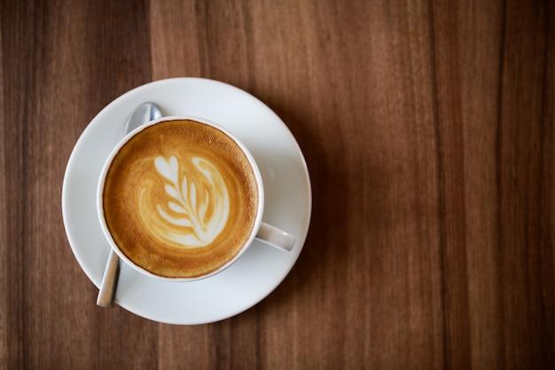 Une tasse de café latte art sur fond de bois