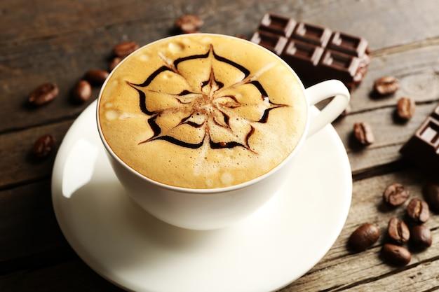 Tasse de café latte art avec grains et chocolat sur table en bois, gros plan