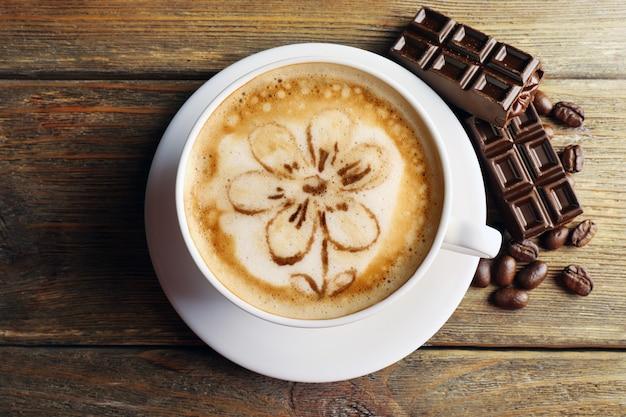 Tasse de café latte art avec grains et chocolat sur table en bois, vue de dessus