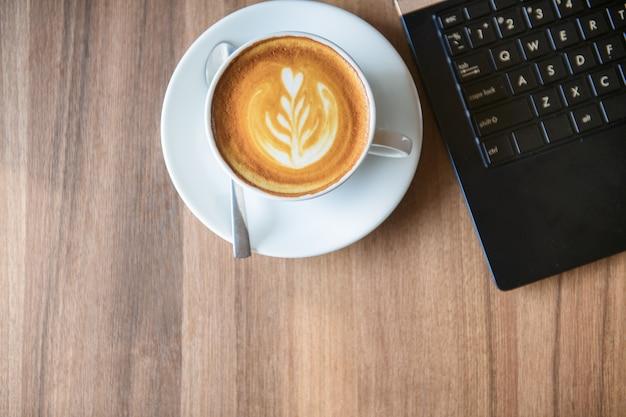 Une tasse de café latte art avec ordinateur portable sur bois