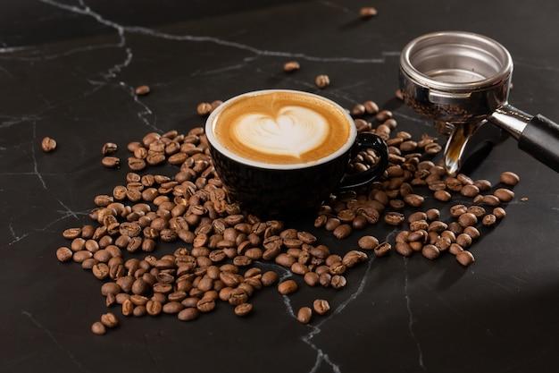Tasse de café latte chaud avec une belle texture d'art latte en mousse de lait avec grain de café sur fond de marbre noir. vue aérienne, copiez l'espace. publicité pour le menu du café. carte du café.