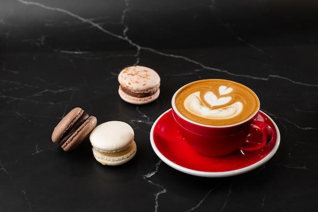 Tasse de café latte chaud avec une belle texture d'art latte en mousse de lait avec macaron français sur fond de marbre noir. vue aérienne, copiez l'espace. publicité pour le menu du café. carte du café.