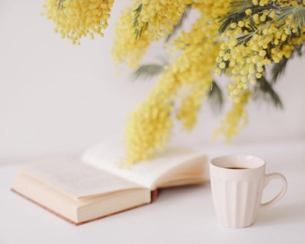Tasse de café et un livre sur un bureau blanc avec bouquet de fleurs jaunes mimosa.