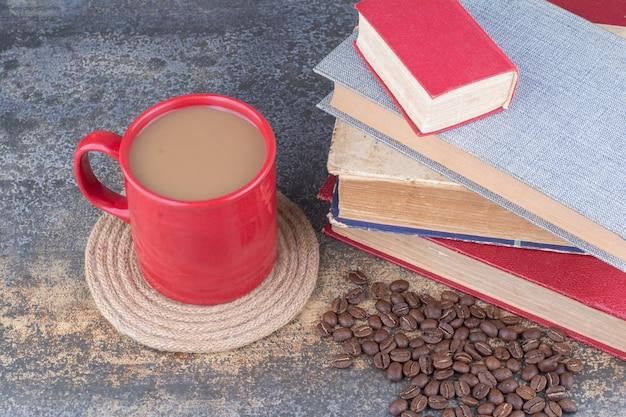 Une tasse de café avec livre et grains de café sur marbre.