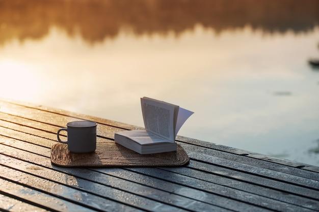 Tasse de café et livre sur la jetée en bois sur le lac d'été