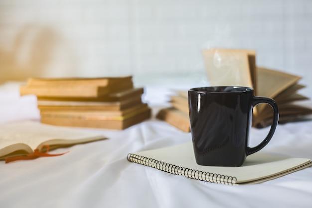 Tasse de café et un livre sur un lit. tasse blanche avec du café sur un livre. fermer