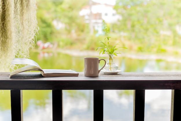 Tasse de café avec un livre ouvert sur un plateau en bois le matin.