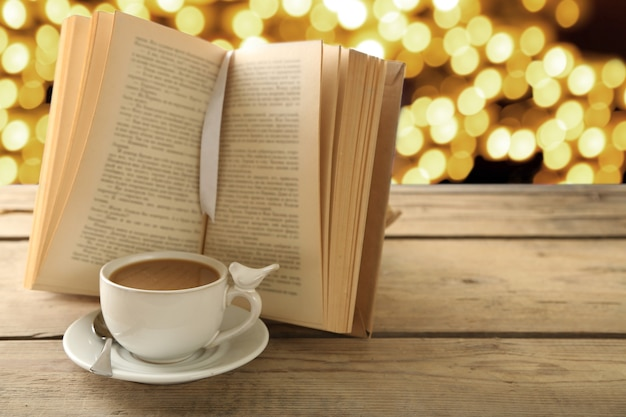 Tasse de café avec livre ouvert sur une surface lumineuse