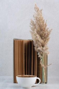 Tasse à café, livre et plante sur table grise