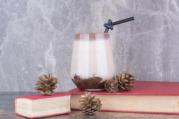 Une tasse de café avec livre et pommes de pin sur marbre.