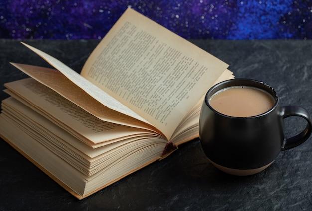 Une tasse de café avec un livre sur une surface sombre.