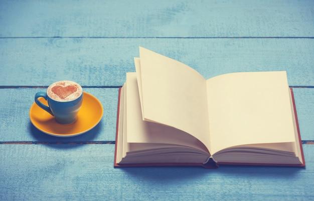 Tasse de café avec livre sur une table en bois bleue.