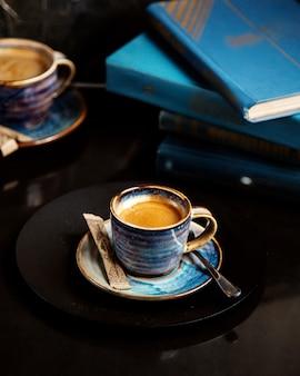 Une tasse de café avec des livres sur la table