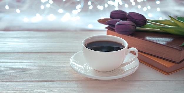 Une tasse de café, des livres et des tulipes sur un fond clair avec des guirlandes lumineuses.