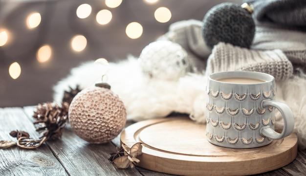 Tasse à café sur les lumières de noël bokeh à la maison sur table en bois avec pull sur un mur et décorations. décoration de vacances, noël magique