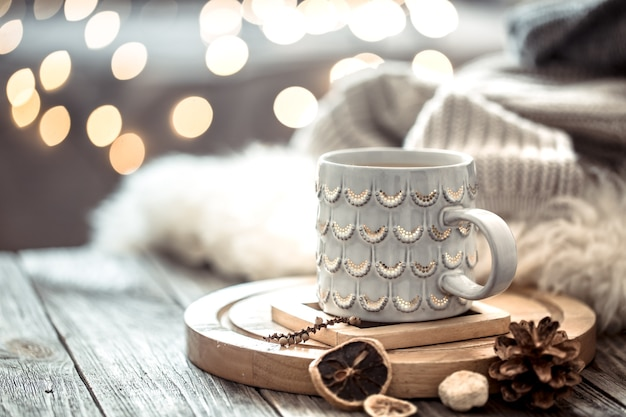 Tasse à café sur les lumières de noël bokeh à la maison sur table en bois avec pull sur un mur et décorations. décoration de vacances