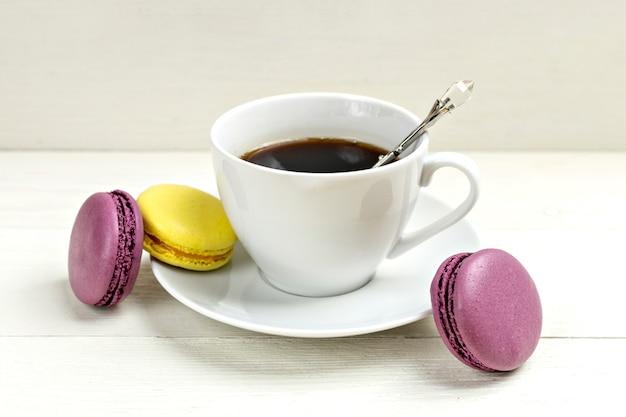 Tasse de café avec macaron sur fond en bois blanc pose à plat