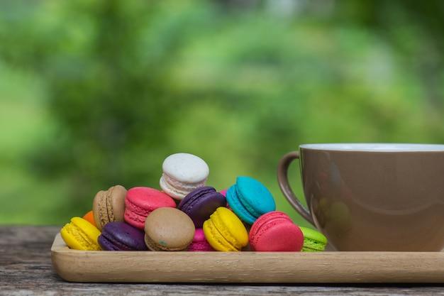 Tasse de café et macarons colorés dans un plat sur une table en bois