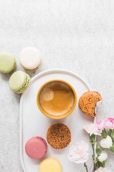 Tasse de café avec des macarons colorés avec des fleurs sur un plateau blanc