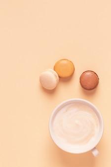 Tasse de café avec des macarons sur fond pastel