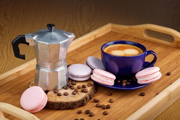 Tasse de café macarons et grains de café sur un plateau et une cafetière geyser sur un plateau en bois