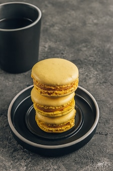Tasse de café et macarons jaunes sur fond gris