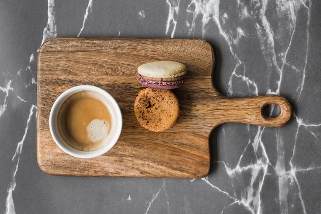 Tasse à café et macarons sur une planche à découper sur le fond de marbre