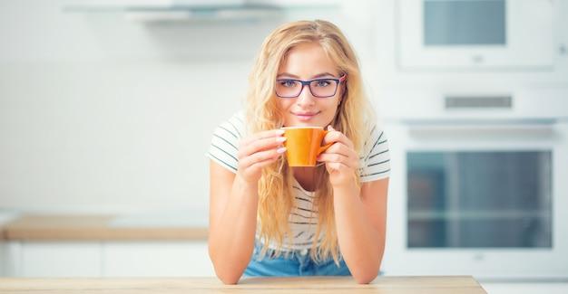 Tasse de café à la main d'une jeune femme heureuse. jolie fille buvant le thé du matin.
