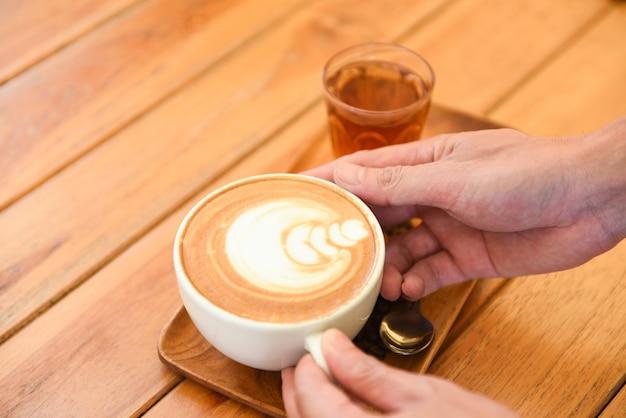 Tasse à café à la main sur une table en bois au café, servi café cappuccino ou latte et thé