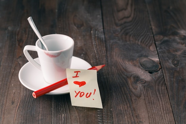 Tasse de café avec marque de rouge à lèvres et note 'je t'aime' sur la table se bouchent