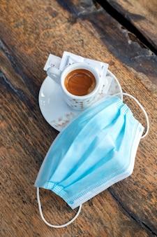 Une tasse de café avec masque sur table en bois