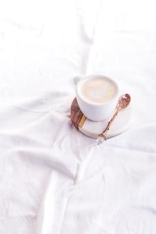 Tasse à café le matin sur le fond du lit blanc, plat poser