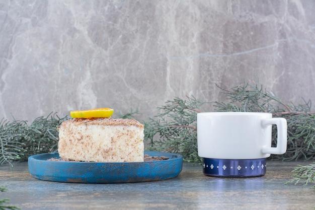 Une tasse de café avec un morceau de gâteau savoureux sur une assiette bleue. photo de haute qualité