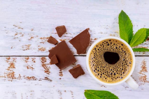 Tasse de café avec des morceaux de mousse, de menthe et de chocolat