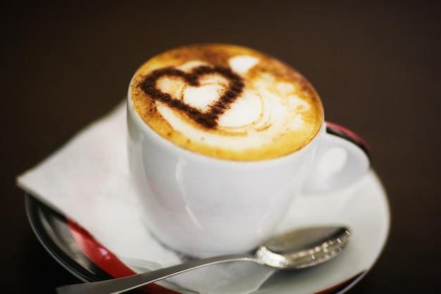 Une tasse de café avec motif coeur dans une tasse blanche sur bois