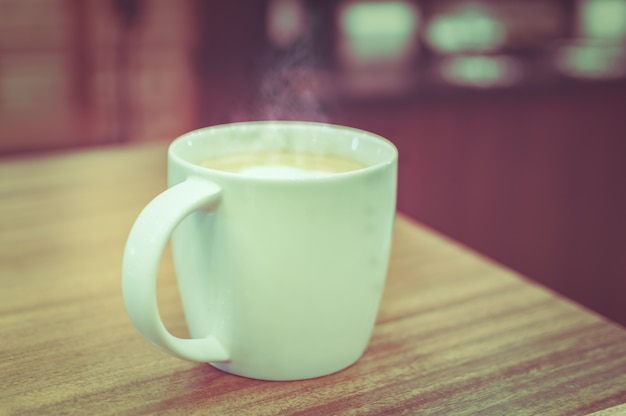 Une tasse de café avec un motif de coeur dans une tasse blanche sur fond de bois. tonalité de mise en scène.