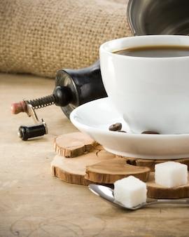 Tasse de café et moulin avec des grains torréfiés