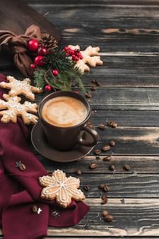 Une tasse de café avec de la mousse sur un bois sombre avec du pain d'épice sous forme de flocons de neige.