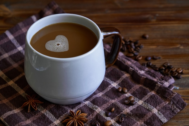 Tasse de café avec une mousse en forme de coeur. avec amour pour le café. sur la surface de la table en bois