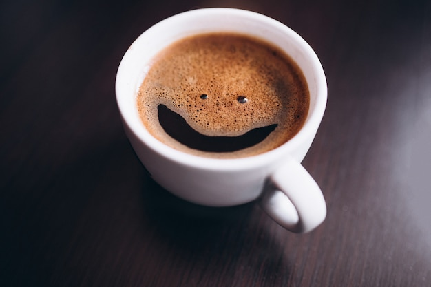Tasse de café avec de la mousse, sourire visage, sur bureau isolé