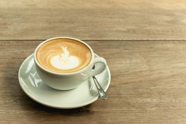 Tasse de café avec de la mousse sur une table en bois.